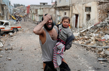 A man cries while he carries his daughter as he walks from Islamic State controlled part of Mosul towards Iraqi special forces soldiers during a battle in Mosul