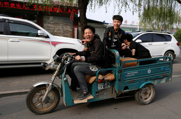Local 17-year-old Liu Zhipeng drives a motor tricycle carrying his friends on a main road in Anxin county