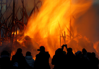 Spectators take pictures of burning installation during the performance devoted to Maslenitsa in the village of Nikola-Lenivets.