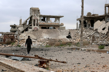 A man walks past damaged buildings in rebel-held area of southern city of Deraa