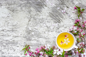 cup of green flower tea and branches of blossoming cherry