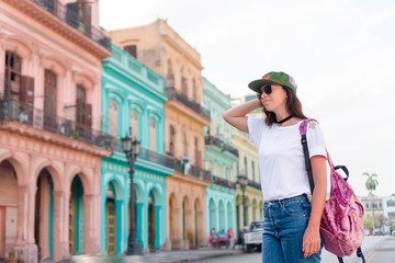 Happy woman in popular area in old Havana, Cuba. Young girltraveler smiling happy background colorful houses