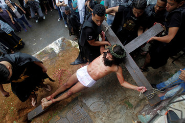 A man portraying the role of Jesus Christ takes part in a procession on Good Friday in Medellin
