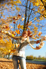 young woman playing with autumn leaves