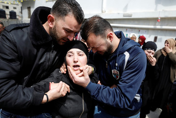 Mother of Palestinian Mohammed Hattab is comforted as she mourns during his funeral in Jalazoun refugee camp near the West Bank city of Ramallah