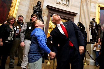 Pence encourages a young tourist to look up at the Capitol rotunda as they cross paths as Pence departs following his meeting with Senate Republicans during their weekly policy luncheon at the U.S. Capitol in Washington