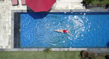 The young beautiful woman swims in the pool, flat lay, dron view...