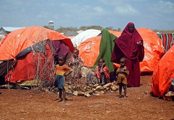 An internally displaced Somali family is seen outside their makeshift shelter at a camp after fleeing from drought stricken regions in Baidoa, west of Somalia's capital Mogadishu