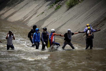 """Opposition demonstrators walk through the river Guaire during clashes with riot police during the so-called """"mother of all marches"""" against Venezuela's President Nicolas Maduro in Caracas"""