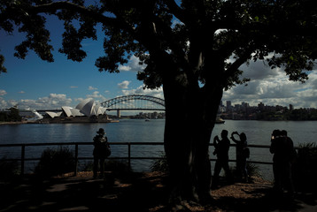 Tourists take pictures of the Sydney Opera House and Harbour Bridge on an early autumn morning in Sydney