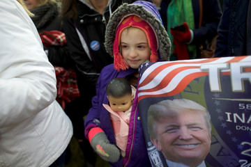 """Gia Morris, 8, carries a doll beside a flag depicting President Donald Trump while posing for a portrait during a """"People 4 Trump"""" rally at Neshaminy State Park in Bensalem"""