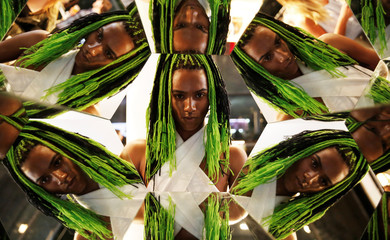 A visitor poses for a picture next to mirrors during Sao Paulo Fashion Week