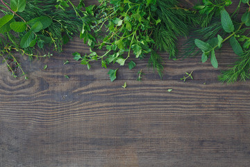 Mix of fresh herbs on wooden background.