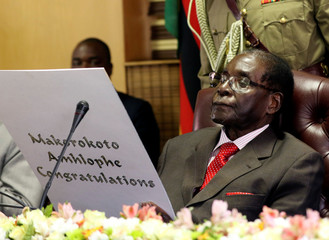 Zimbabwe's President Robert Mugabe reads a card during his 93rd birthday celebrations in Harare
