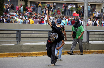 A demonstrator throws a rock during clashes with riot police at a rally in Caracas, Venezuela