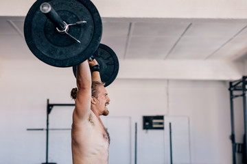 Muscular man lifting heavy barbell at gym