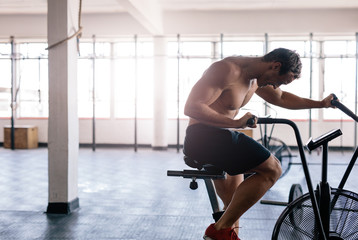 Man cycling on stationary bicycle in the gym
