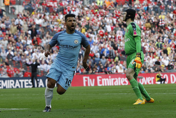 Manchester City's Sergio Aguero celebrates scoring their first goal as Arsenal's Petr Cech looks on dejected