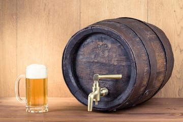 Glass of beer and old oak wood barrel