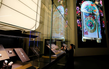 A woman takes a picture of a display window of Patek Philippe at the Baselworld watch and jewellery fair in Basel