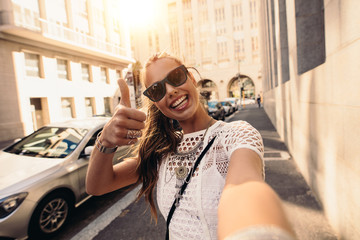 Tourist taking selfie in a street surrounded by buildings.