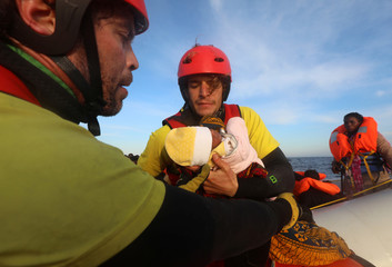 Spanish rescuer Daniel Calvelo hands over a four-day-old baby girl to his colleague Asier Renedo  during a search and rescue operation by Spanish NGO Proactiva Open Arms, in central Mediterranean Sea