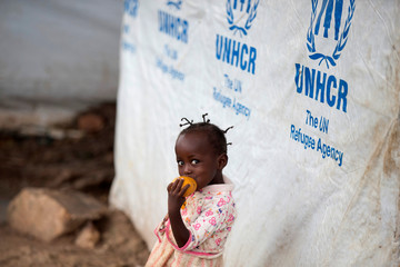 A girl eats a mango at a shelter for displaced people in Bangui