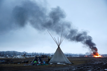 A building burns after it was set alight by protesters preparing to evacuate the main opposition camp against the Dakota Access oil pipeline near Cannon Ball