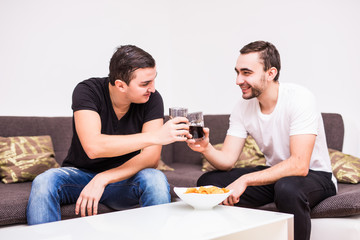 Two friends having a glass of whiskey cheers and some quality time together at home
