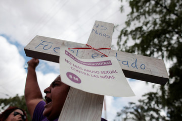 An activist protests outside of Guatemala's embassy in Managua