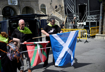 Organizers fold Basque and Scottish flags during the Basque nationalist celebration Aberri Eguna (Fatherland Day), organised by the Red Independistak (Independence Network), in Guernica