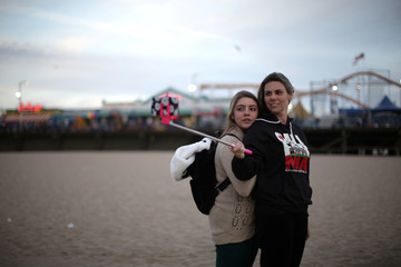 Camila Breda, 39, and her daughter Giovanna Kreischer, 13, hold a selfie stick as they pose for an iPhone photo by the Pacific Ocean on a cold spring solstice day in Santa Monica
