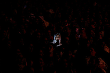 Light from a mobile phone illuminates a Saudi woman's face during Iraqi singer Majid Al Muhandis' live performance as part of Spring of Culture 2017 in Manama