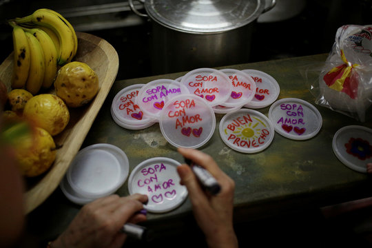 """Lids with messages that read """"soup with love"""" are seen at the home kitchen of a volunteer of Make The Difference (Haz La Diferencia) charity initiative, in Caracas"""