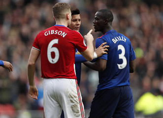 Manchester United's Eric Bailly clashes with Middlesbrough's Ben Gibson as Marcos Rojo looks on