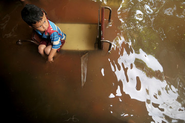A child sit on a chair as flood hit his house at Sidakaton district in Tegal