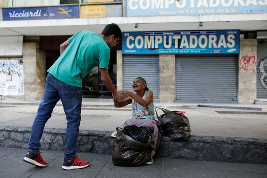 Mariano Marquez, a volunteer of Make The Difference (Haz La Diferencia) charity initiative, gives a cup of soup and an arepa to a homeless woman in a street of Caracas
