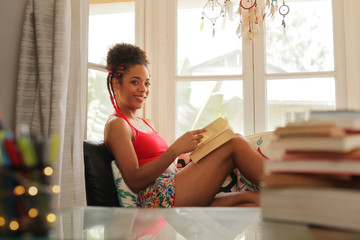 Portrait Black Woman Reading Book And Smiling At Camera