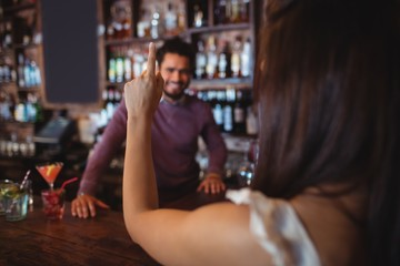 Woman asking for a drink to bar tender