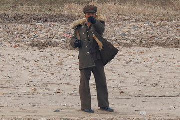 A North Korean soldier gestures from the North Korean side of the Yalu River towards a Chinese boat carrying tourists near Sinuiju