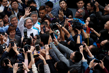 Chief Executive candidate and former Financial Secretary John Tsang waves to supporters during an election campaign in Hong Kong, China