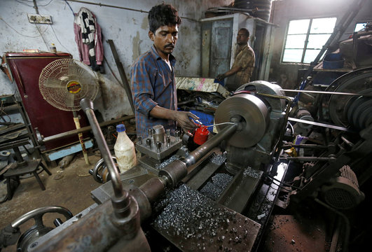 A man works on a lathe as he makes stone cutting tools inside a manufacturing unit in Ahmedabad