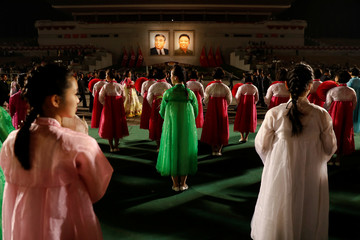 Portraits of North Korea founder Kim Il Sung and late leader Kim Jong Il glow as people take part in a mass dance event marking the 105th birth anniversary of Kim Il Sung in Pyongyang