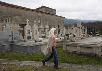 "A reveller walks through a graveyard during the ""O Entroido"" festival in the village of Laza"