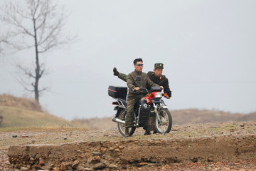 A North Korean soldier climbs off of a motorcycle in Sinuiju, North Korea, which borders Dandong