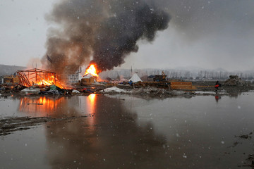 Buildings burn after being set alight by protesters preparing to evacuate the main opposition camp against the Dakota Access oil pipeline near Cannon Ball