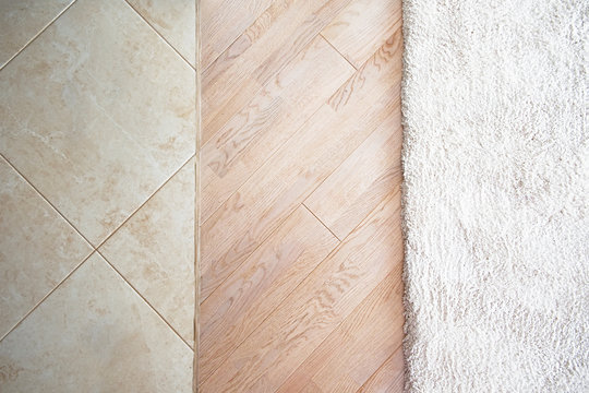 Floor with marble tile pattern, laminate parquete floor with beige soft carpet