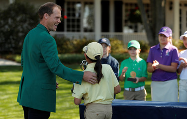 Lucy Yuan receives gets a pat on the back from 2016 Masters champion Danny Willett after winning the 10-11 year-old girls  division following the Drive, Pitch and Putt National Finals at Augusta National Golf Course,in Augusta