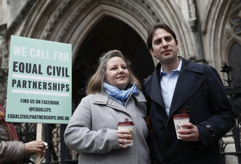 Rebecca Steinfeld and Charles Keidan pose for a photograph outside the Royal Courts of Justice in central London