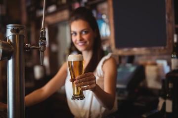 Female bar tender holding glass of beer